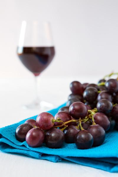 zblizenie kilka czerwonych winogron i kieliszek