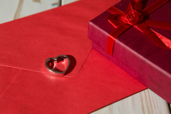 zblizenie srebrnego wisiorka na czerwonej kopercie
