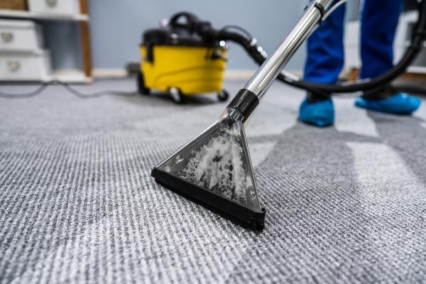 osoba czyszczaca dywan z odkurzaczem