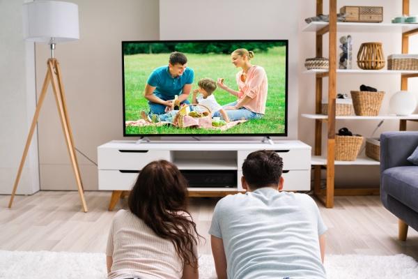 szczesliwa rodzina ogladajaca telewizje lub film