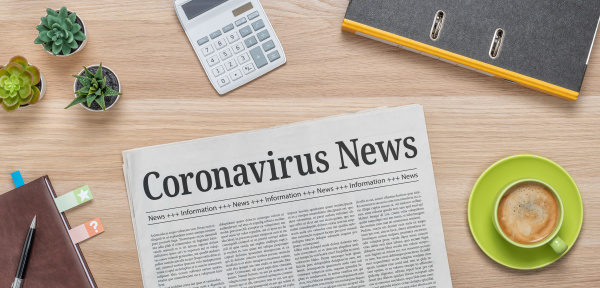 gazeta na biurku z naglowkiem coronavirus