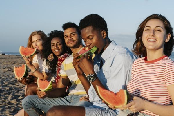 przyjaciele cieszacy sie jedzeniem kawalka arbuza