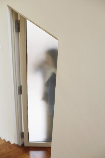 kobieta stojaca za drzwiami
