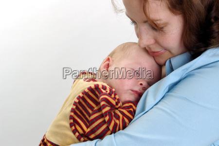 dziecko spi w ramionach matki