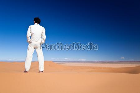 czlowiek stojacy na pustynnej wydmie