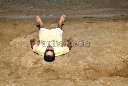 man lying on beach