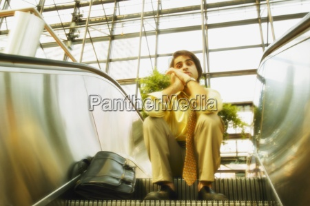 man sits on an escalator
