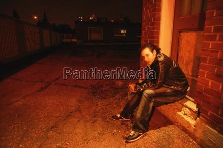 man sits under street light