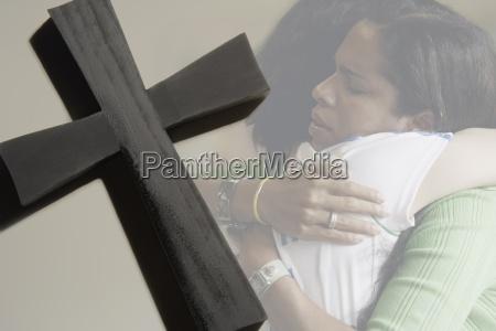 women hugging cross