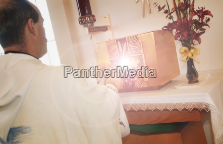 priest stands in front of glowing