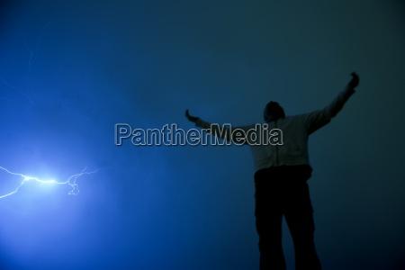 czlowiek z wyciagnietymi ramionami w burzy