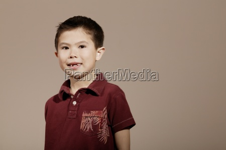 little boy smiling and posed wearing