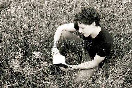 czlowiek czytajacy w trawie