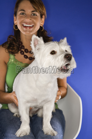 woman holding white terrier dog