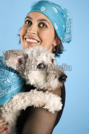 smiling young woman holding dog