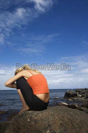 kobieta siedzi na skalistym brzegu
