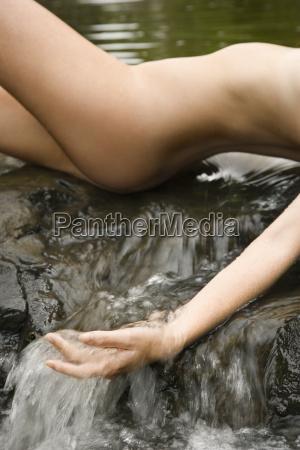 nude woman in stream