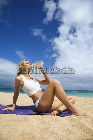 attractive young woman drinking on beach