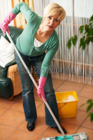 kobieta ociera podlogi w domu