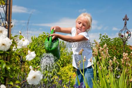 dziewczynka leje kwiaty