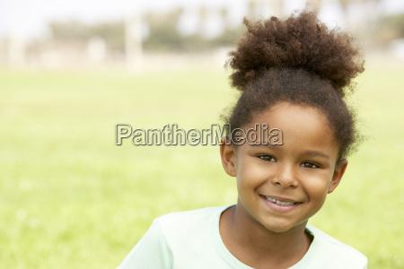 portret mlodej dziewczyny siedzacej w parku