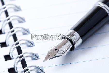 czarny dlugopis i notatnik