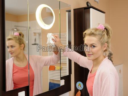 gospodyni domowa czysci lustro w lazience