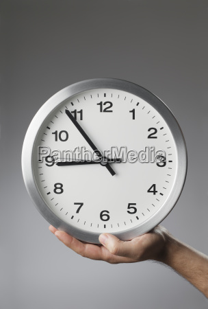 man holding a clock in his