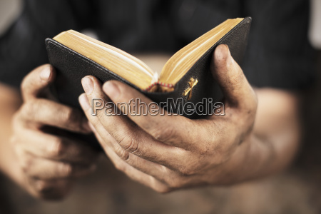 dirty hands holding an old bible