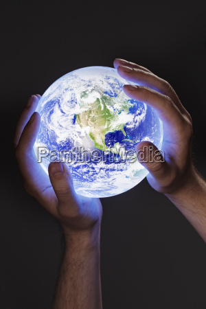 man holding a glowing earth globe