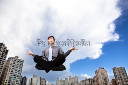 businessman meditating in the air before