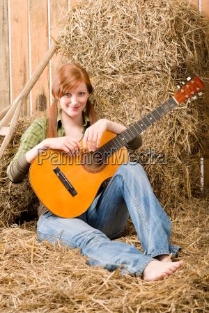 mloda kobieta kraj siedzi na siano