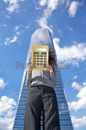 calculator businesswoman and skyscraper