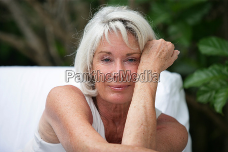 szary wlosach kobieta siedziala w ogrodzie