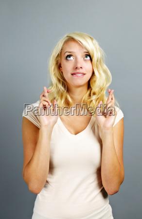 pelna nadziei kobieta krzyzuje palce