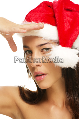 young woman wearing santa hat looks