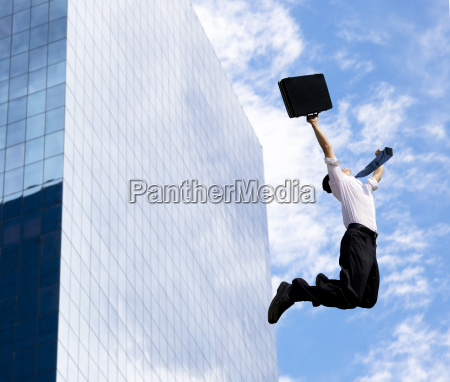 happy businessman jumping in front of
