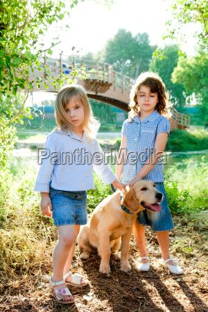 kid girls with golden retriever puppy