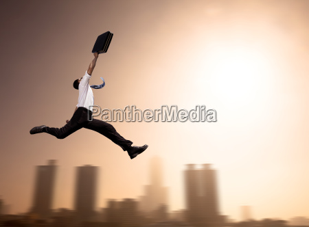excited businessman running with cityscape background