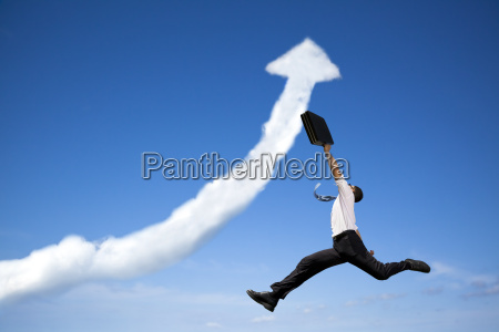 jumping businessman with business growing graph