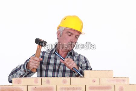 robotnik za pomoca mlotka i dluta