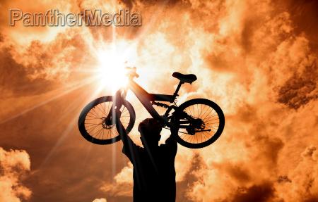 the silhouette of mountain biker raised