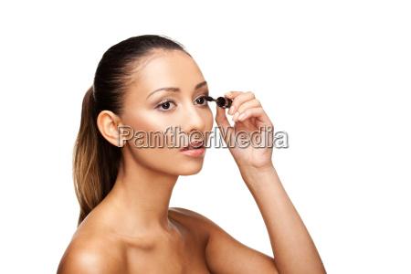 beautiful woman applying mascara