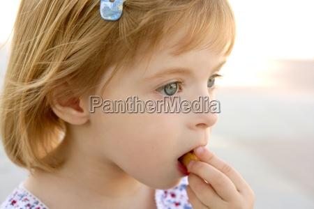 blond little girl closeup portrait eating