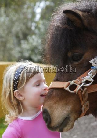 little blond girl loves her donkey