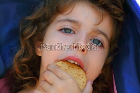 little girl eating biscuit closeup portrait