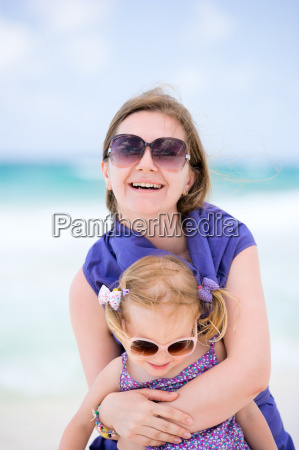 happy mother and daughter at beach