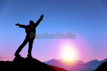 mlody czlowiek stojacy na szczycie gory