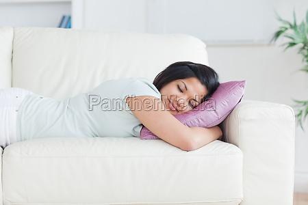 kobieta spi na kanapie z poduszka