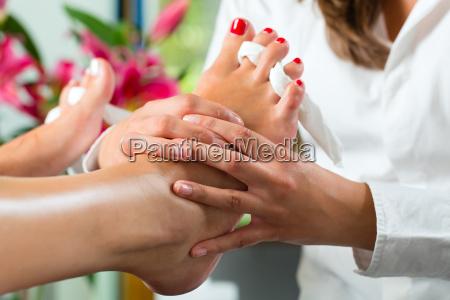 kobieta w salonie pieknosci otrzymuje pedicure